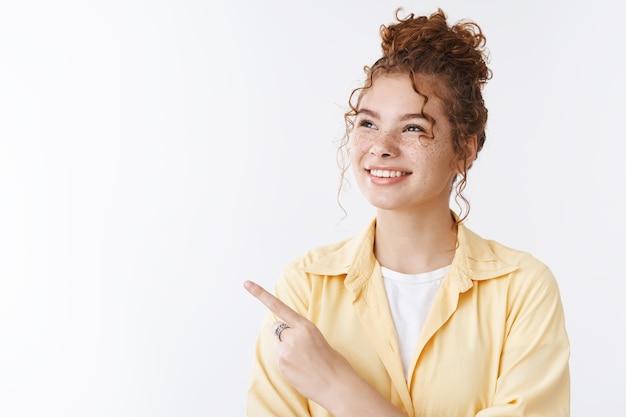 Rozmarzona rozbawiona atrakcyjna szczęśliwa rudowłosa studentka śniąca świetlana pomyślna przyszłość wpatrująca się w niebiosa zaintrygowana zdumiona w lewym górnym rogu uśmiechnięta szeroko zainteresowana reklama produktu