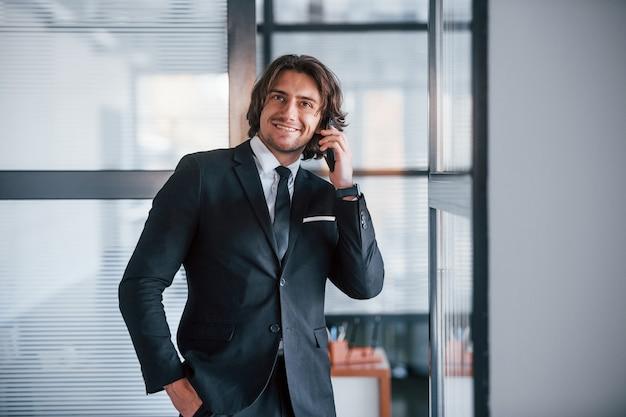 Rozmawia przez telefon w biurze. portret przystojny młody biznesmen w czarnym garniturze i krawat.