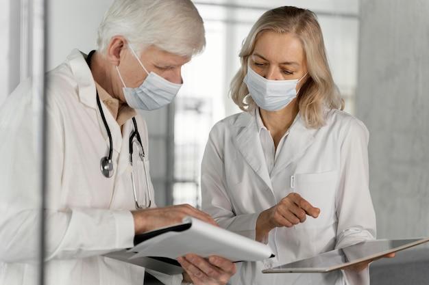 Rozmawiają lekarze w maskach medycznych