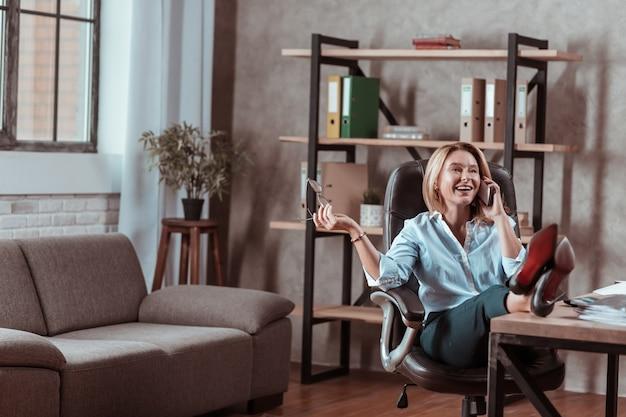 Rozmawiając przez telefon. stylowa dojrzała bizneswoman w butach na wysokim obcasie rozmawiająca przez telefon