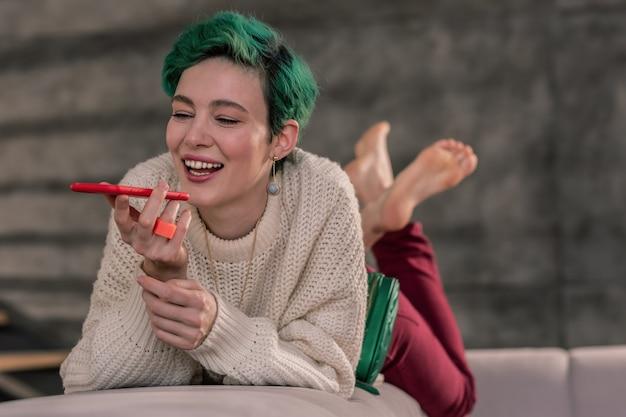 Rozmawiając z przyjacielem. pozytywna kobieta w dobrym nastroju trzymająca czerwony smartfon i rozmawiająca z przyjaciółką