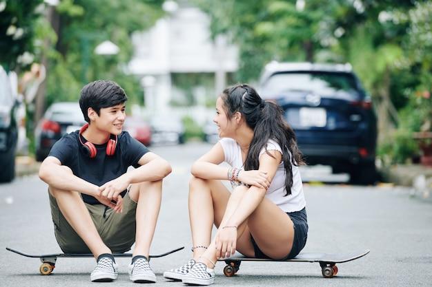 Rozmawiające nastolatki siedzące na deskorolkach