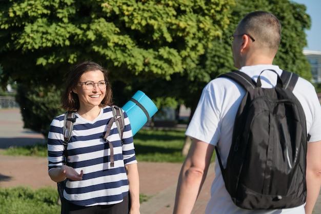 Rozmawiający mężczyzna i kobieta w średnim wieku, para spacerująca wzdłuż ulicy w parku na trening fitness