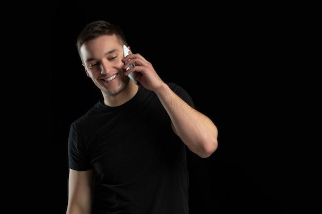 Rozmawiam przez telefon. monochromatyczny portret młodego mężczyzny kaukaski na białym tle na ścianie czarnego studia.