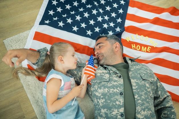 Rozmawiam z córką. szczęśliwy bohaterski sługa wojskowy czuje się wzruszający, rozmawiając ze swoją małą córeczką
