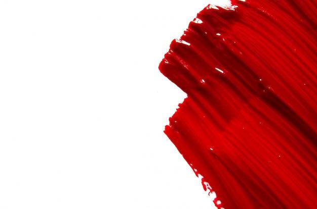 Rozmaz i tekstura czerwona szminka lub farba akrylowa na białym tle.