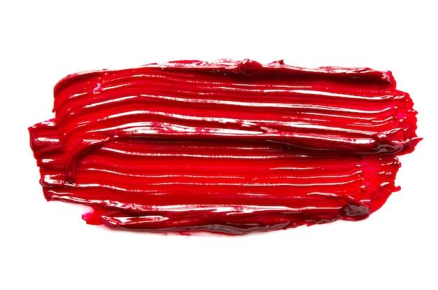 Rozmaz i tekstura czerwona szminka lub farba olejna na białym tle.