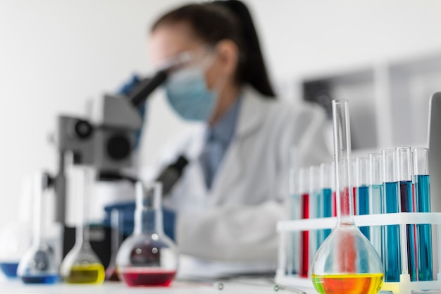 Rozmazana kobieta patrząc przez mikroskop