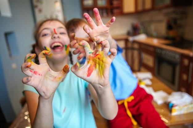 Rozmazani farbą dzieci, chłopiec i dziewczynka, wygłupiają się i śmieją w kuchni z rozpostartymi ramionami