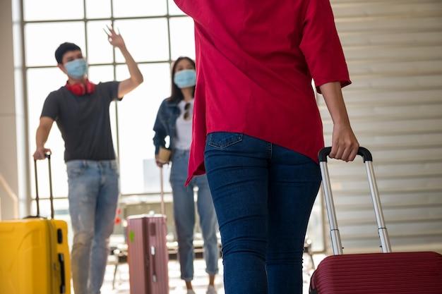 Rozmazani młodzi przyjaciele podnoszą ręce, by przywitać się z dziewczyną, która ciągnie bagaż na terminalu odlotów lotniska.