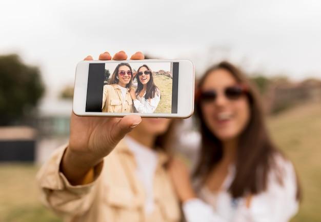 Rozmazani przyjaciele trzymający smartfon