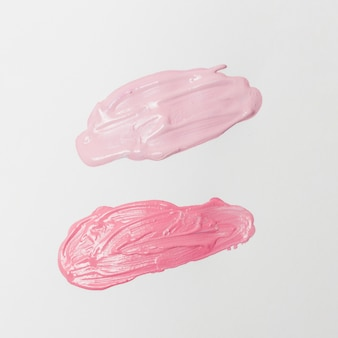 Rozmazy różowych pomadek na szarym tle