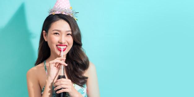 Rozmiar banera. moda ładna kobieta pije colę z butelki na kolorowym niebieskim tle