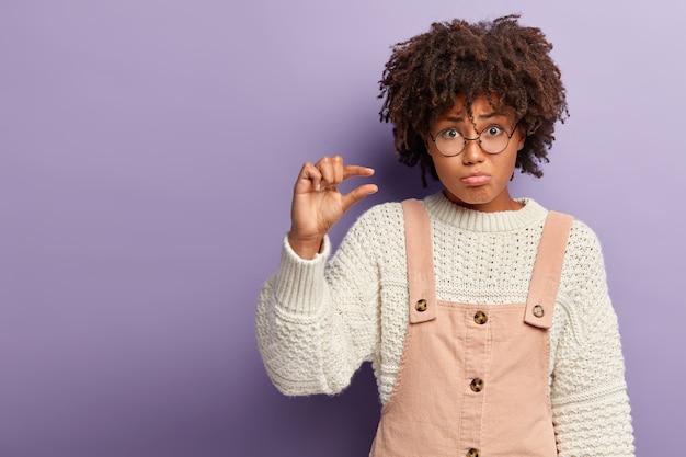 Rozmiar ma znaczenie. niewzruszona niezadowolona dama kształtuje mały przedmiot, otrzymuje niewielkie pieniądze na konto, nosi okrągłe okulary, stylową odzież, niezadowolona z czegoś malutkiego, rozczarowana