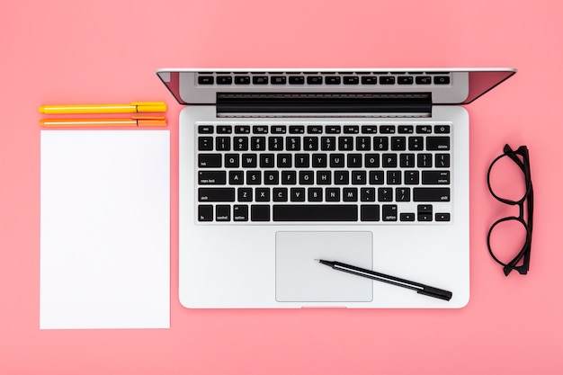 Rozmieszczenie elementów biurka na różowym tle