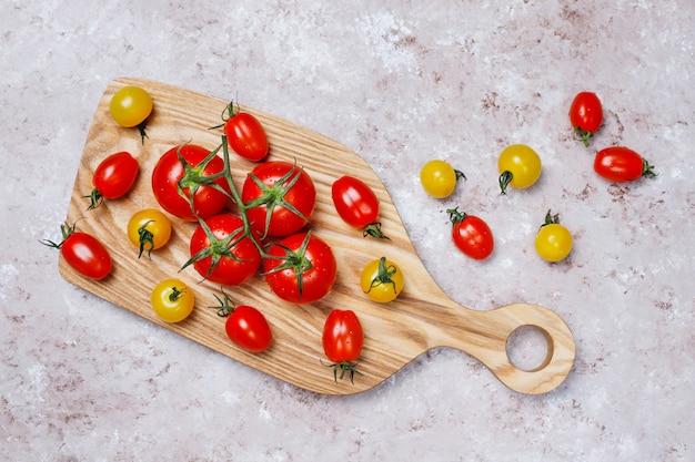 Rozmieszczenie kolorowych świeżych bukietów pomidorów na powierzchni betonu