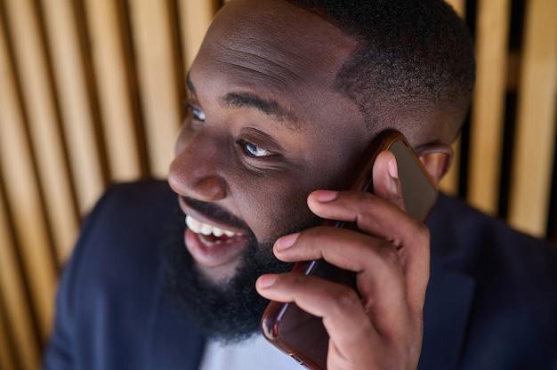 Rozmowa biznesowa. ciemnoskóry biznesmen rozmawia przez telefon i wygląda na zaangażowanego