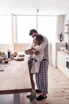 Rozmowa. dość długowłosa młoda kobieta ubrana w białą koszulę i rozmawiający z mężem w kuchni