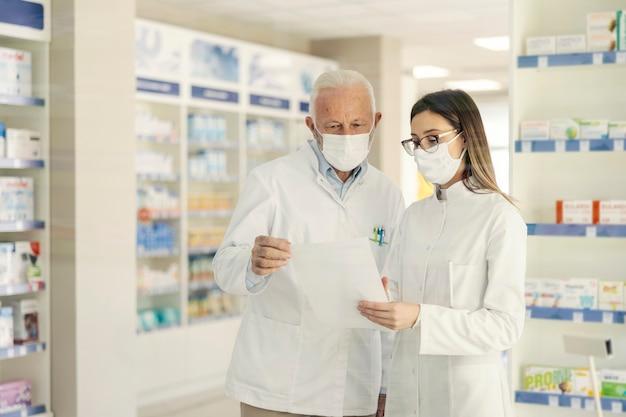 Rozmowa dwóch farmaceutów z koronawirusem. przed przejściem na emeryturę farmaceuta wyjaśnia młodemu farmaceucie dokumentację w aptece. noszą mundury i maski na twarz