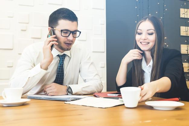 Rozmowa dwóch pracowników biurowych. zespół pracujący wewnątrz. mężczyzna rozmawiający ze smartfonem.