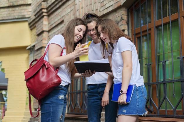 Rozmowa grupa dziewcząt studenckich, nastoletnich studentów college'u w pobliżu budynku z cegły. powrót na studia, początek zajęć, edukacja, liceum