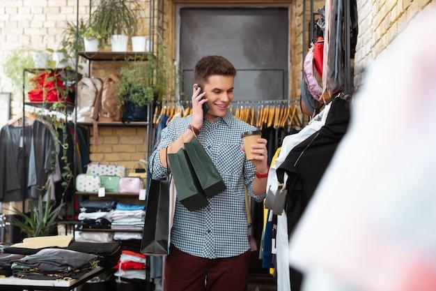 Rozmowa i uśmiech. emocjonalny pozytywny młody człowiek trzyma papierowe torby i uśmiecha się podczas rozmowy przez telefon w sklepie z ubraniami