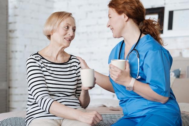 Rozmowa jako terapia. godna podziwu piękna pozytywna pani oferująca młodej damie filiżankę herbaty na znak wdzięczności za pomoc w wyzdrowieniu z choroby
