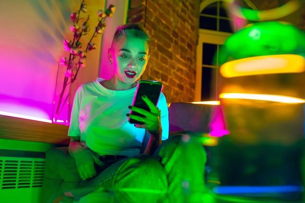Rozmowa. kinowy portret stylowej kobiety w oświetlonym neonami wnętrzu. stonowane jak efekty kinowe, jaskrawe, neonowe kolory. kaukaski model za pomocą smartfona w kolorowych światłach w pomieszczeniu. kultura młodzieżowa.