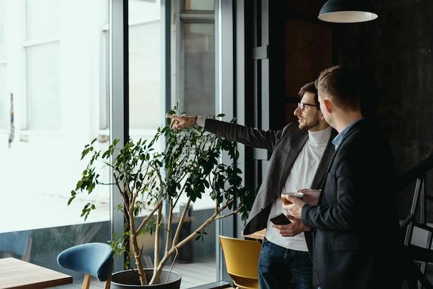 Rozmowa ludzi biznesu, wskazując ręką na okno