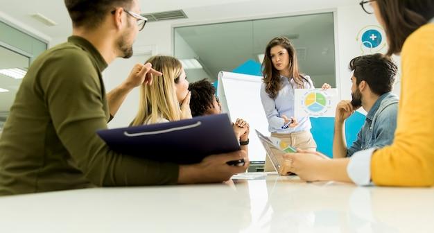 Rozmowa między młodymi pracownikami w małej firmie startupowej z kartką papieru
