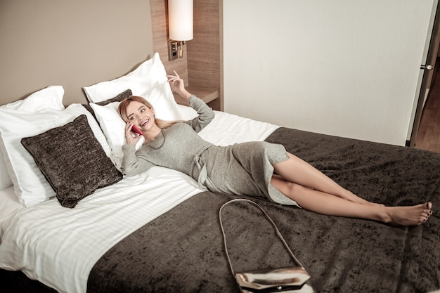 Rozmowa telefoniczna. szczupła piękna blondynka na sobie długą szarą sukienkę po rozmowie telefonicznej