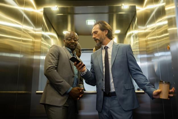 Rozmowa z partnerem. siwy mężczyzna rozmawiający z partnerem biznesowym podczas korzystania z windy w centrum biznesowym