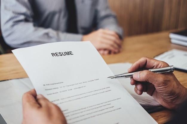 Rozmowa z pracodawcą pyta młodego mężczyznę poszukującego pracy o rekrutację w biurze