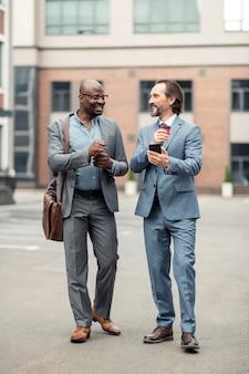 Rozmowa z pracownikiem. siwy biznesmen trzymający smartfona rozmawiającego ze swoim pracownikiem pijącym kawę
