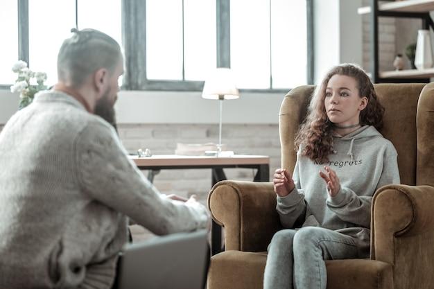 Rozmowa z psychologiem. atrakcyjna kręcona nastolatka rozmawiająca z profesjonalnym psychologiem po szkole