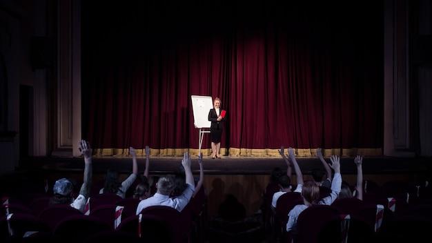 Rozmowa ze studentami. kobieta mówca dając prezentację w hali w warsztatach. centrum biznesowe. widok z tyłu uczestników na widowni. impreza konferencyjna, szkolenie.