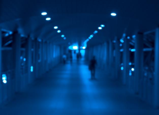 Rozmycie abstrakcyjnego fragmentu miasta z oświetlonymi ludźmi idącymi w nocy. niebieski obraz stonowany.