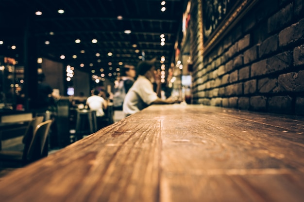 Rozmycie drewnianego stołu barowego w nocnej kawiarni / selektywne obrazy ostrości