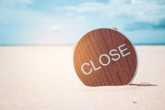 Rozmycie letniej plaży bokeh z metaforą zamkniętego znaku, że lato lub plaża nie jest otwarta.