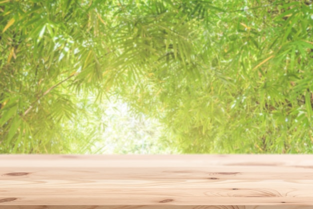 Rozmycie liścia bambusa zielony charakter z drewnianym stołem do wyświetlania w tle naturalnego ekologicznego produktu.