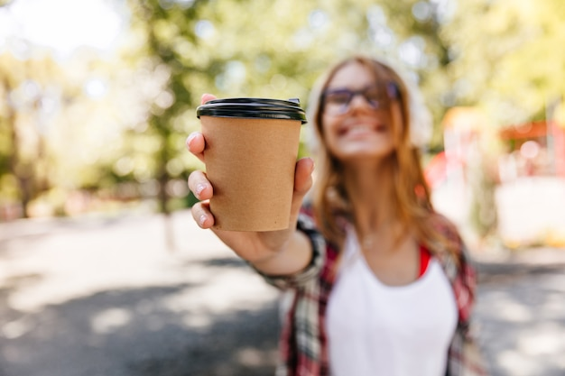 Rozmycie portret uroczej kobiety trzymającej filiżankę kawy. beztroska stylowa dziewczyna korzystających z letniego dnia.