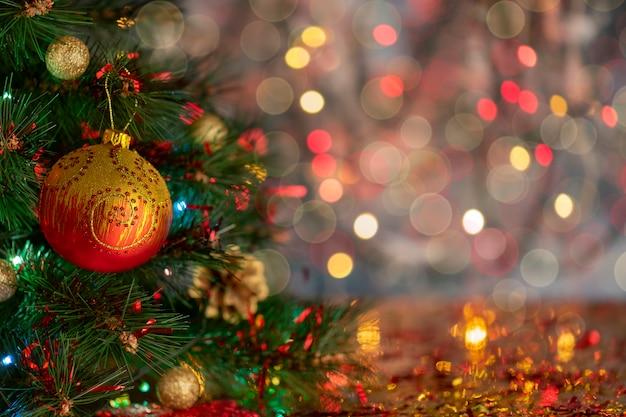 Rozmycie streszczenie złota bożenarodzeniowa piłka z simbol nowy rok na drzewnym bokeh tle. święta bożego narodzenia tło z miejsca kopiowania tekstu. nieostrość