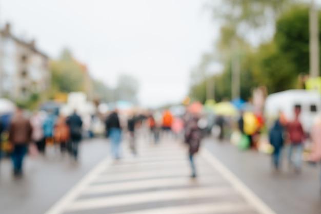 Rozmycie tła ludzi, tłum nierozpoznawalnych ludzi przechodzących przez drogę na zewnątrz nieostrości.