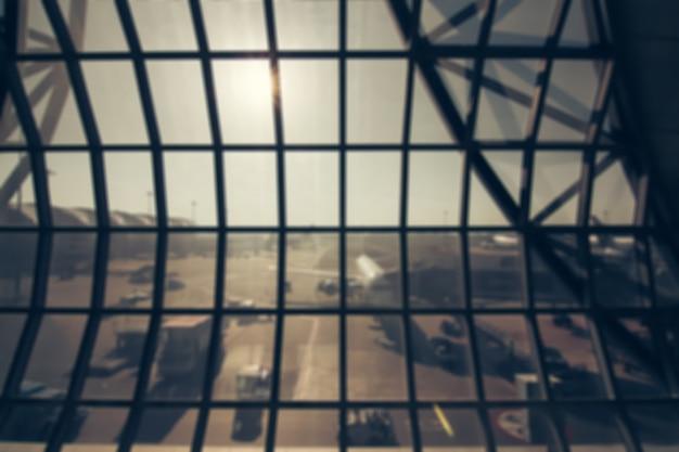Rozmycie tła: pasażer oczekiwanie na lot na terminalu lotniska rozmycie tła z światła bokeh.
