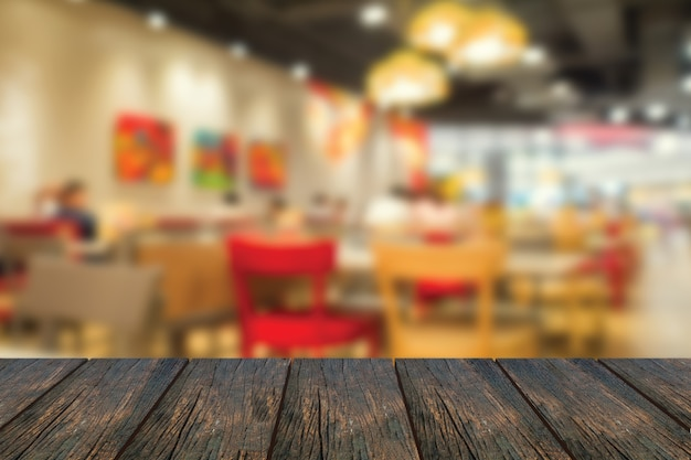Rozmycie wewnątrz restauracji ze stołem z drewna na pierwszym planie.