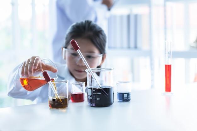 Rozmycie zdjęć azjatyckiej dziewczyny uczenie się i przeprowadzenie eksperymentu naukowego
