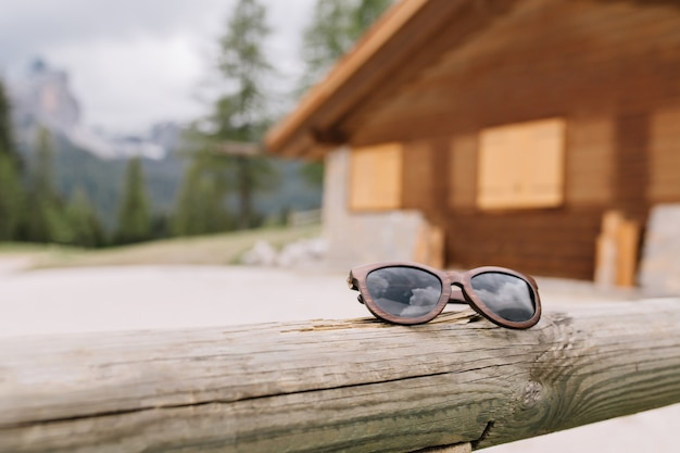 Rozmycie zdjęcia górskiego drewnianego domu w lesie z modnymi okularami przeciwsłonecznymi na pierwszym planie