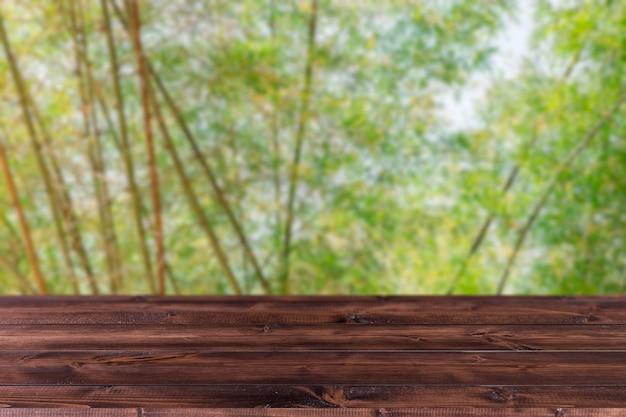 Rozmycie zielone drzewo bambusowy gaj las z drewnianą przestrzenią forground dla produktów montaż tła reklamowego.