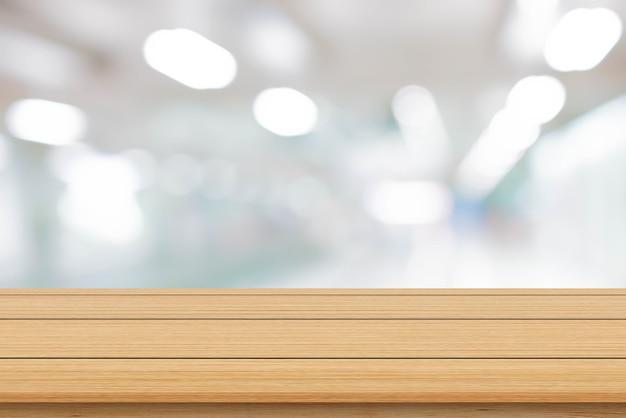 Rozmyj wnętrze biura z nowoczesnym drewnianym stołem do wyświetlania reklam