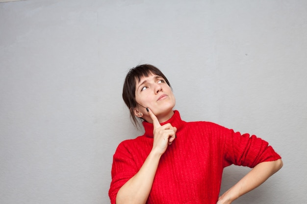 Rozmyślająca kobieta w czerwonym swetrze oparła kijem o czoło szarej ściany